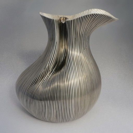 The Sterling Water Pitcher ($39,000) was made in response to my desire to create a vessel where the very shape of the piece serves as its handle.  The only way I could imagine achieving such a complex form was to build it. This I did using 241 strands of round wire shaped and soldered side by side.  The resulting surface texture pleases me very much. It looks both classic like a Greek column and organic like blades of grass side by side.    My website includes a process series of this piece.