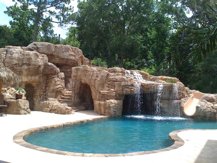 Great waterfall into pool with hidden grotto and a slide for Piscine a deversement