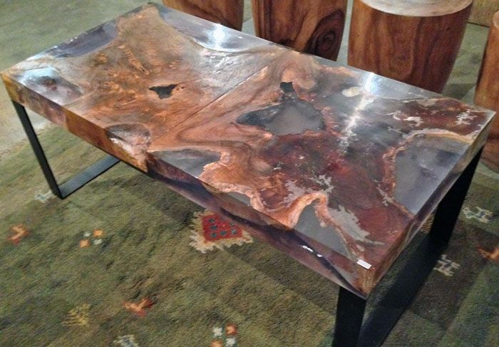a coffee table made from reclaimed old growth teak tree trunk section and resin on steel legs