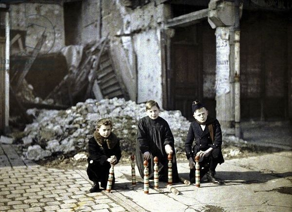 Three children playing with bowling pins at the Place Drouet d'Erlon, Reims, Marne, France, 1917 (autochrome)