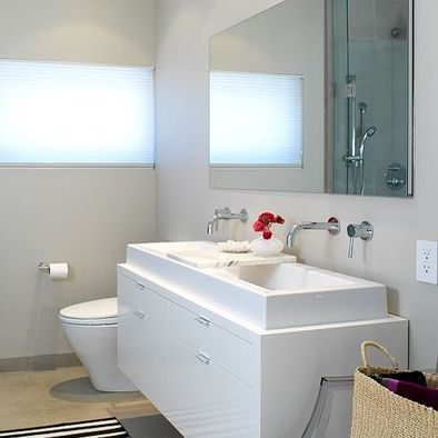 Shared Bathroom: Long sink on top of floating white cabinety with wall mounted faucets - would look great with a gray colored floor tile.