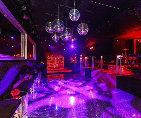 Cool Disco balls dim lighting and metallic benches topped with dark velvet cushions create a