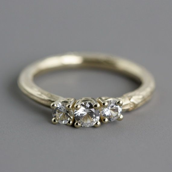 Este anillo de compromiso de zafiro blanco de 3 piedras con forma de ramita: | 32 Anillos de compromiso asombrosos que no tienen nigún diamante