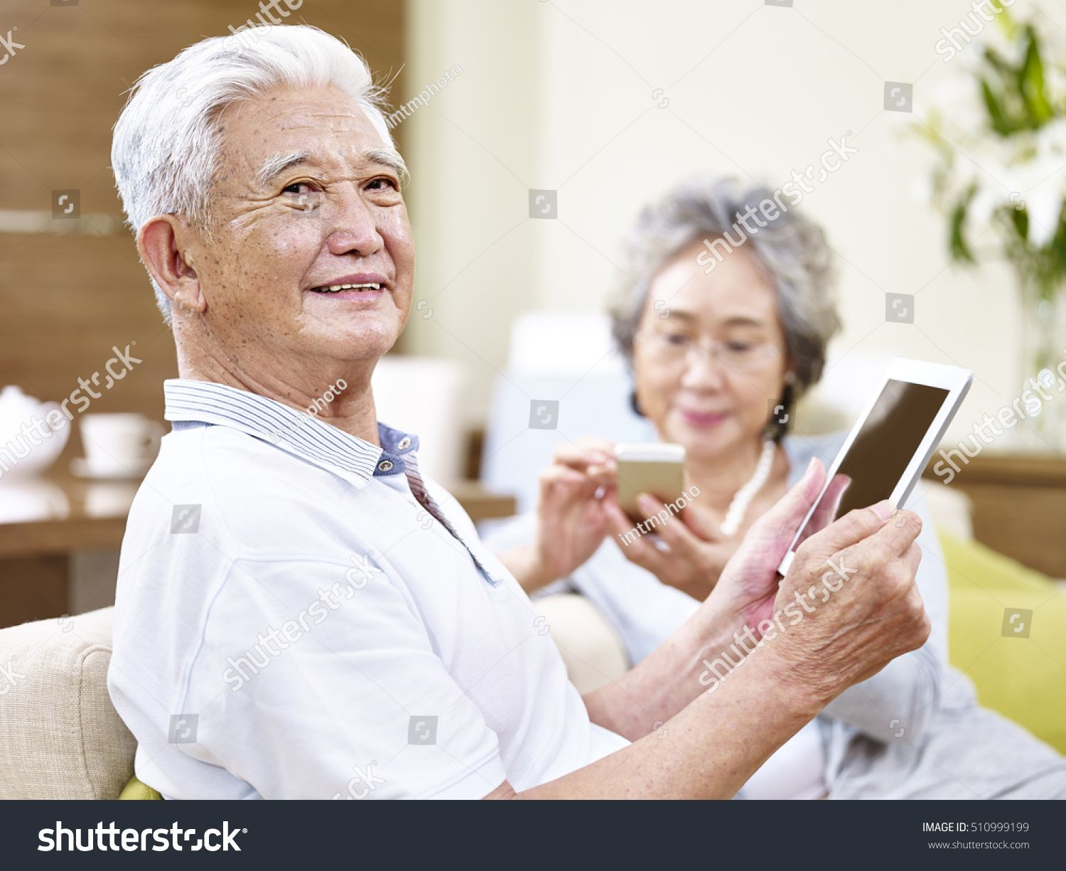 senior asian couple sitting on couch enjoying modern technology using tablet computer and cellphone #Ad , #SPONSORED, #sitting#couch#couple#senior