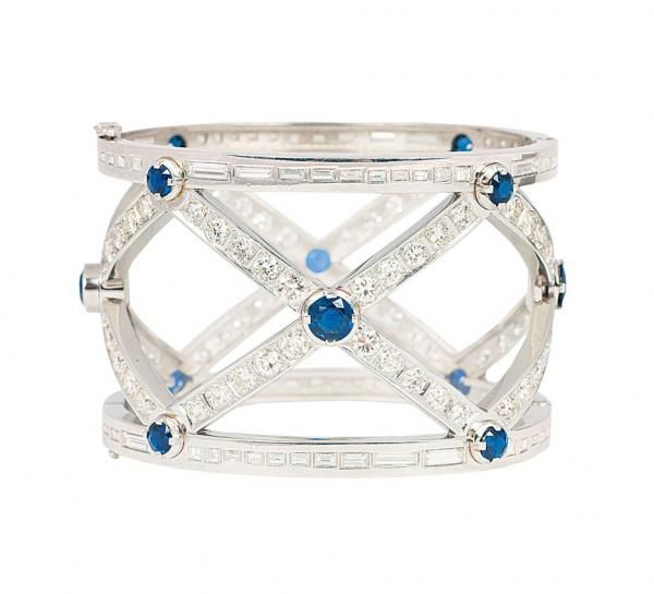 An extraordinary platinum bangle bracelet with diamonds and sapphires  London, 1995. Platinum, marked, makers mark: AD. Wide bangle bracelet with crosswise in design, all around with 168 diam. in baguette and carrée cut in total approx. 18 ct. G-H.vvsi-si. and with 12 sapphires in round cut. W. 45 mm, inside measurements 48 x 56 mm, weight approx. 155 g AUKTIONSHAUS STAHL, HAMBURG - ALLEMAGNE Estimation 16.000€