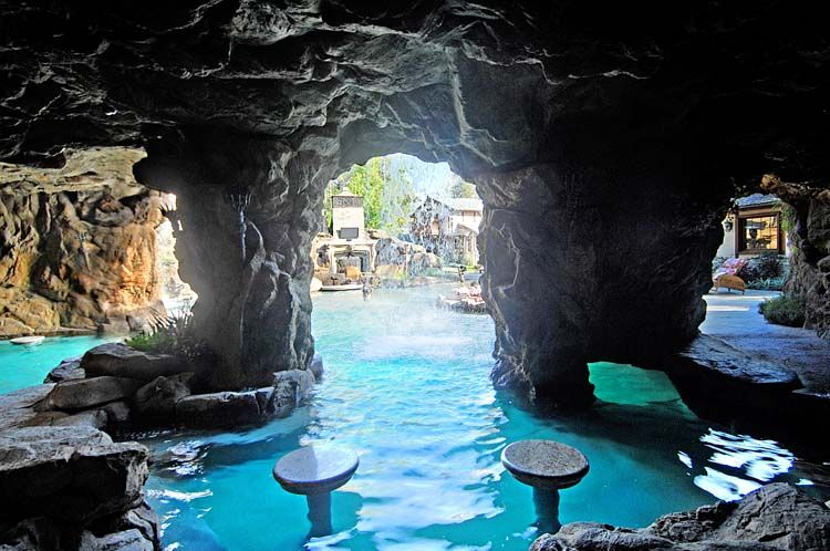 Pool cave behind a waterfall with seating Pools \ Spa