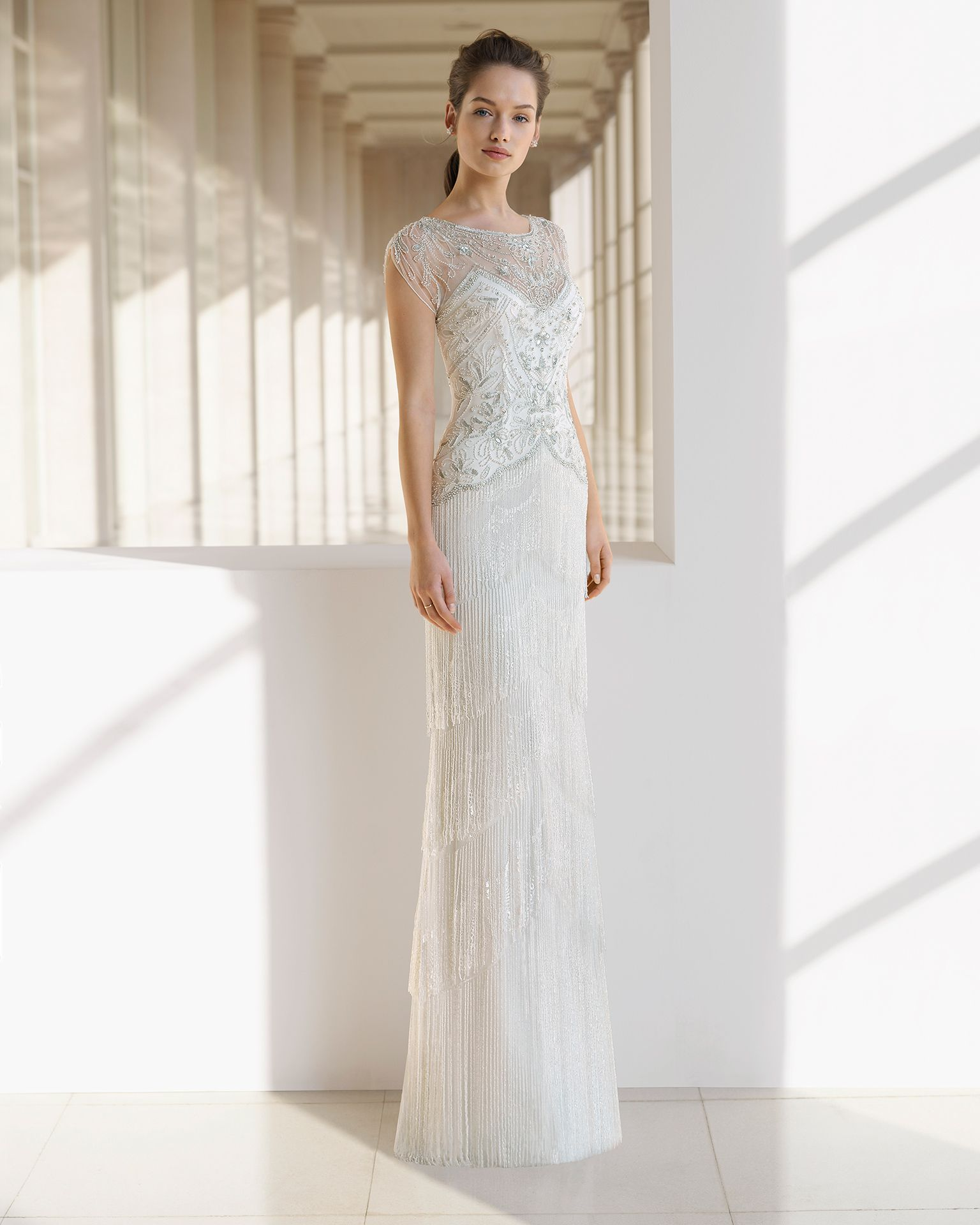 d00389fc7bf Sheath-style wedding dress with beading and fringe. Illusion neckline with  beaded embroidery and short sleeves. Available in natural silver and  natural.