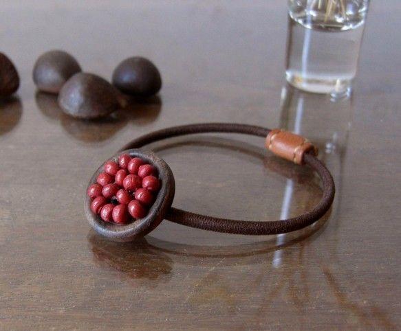木の実のようなヘアゴムです。/ 色 /ダークブラウン×深い赤(ゴム:こげ茶)/ サイズ /ボタン直径 約23mm/ 素材 / ウッドビーズ、ウッド... ハンドメイド、手作り、手仕事品の通販・販売・購入ならCreema。