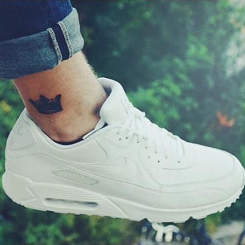 Pequeo tatuaje de una corona en el tobillo de David Lovric