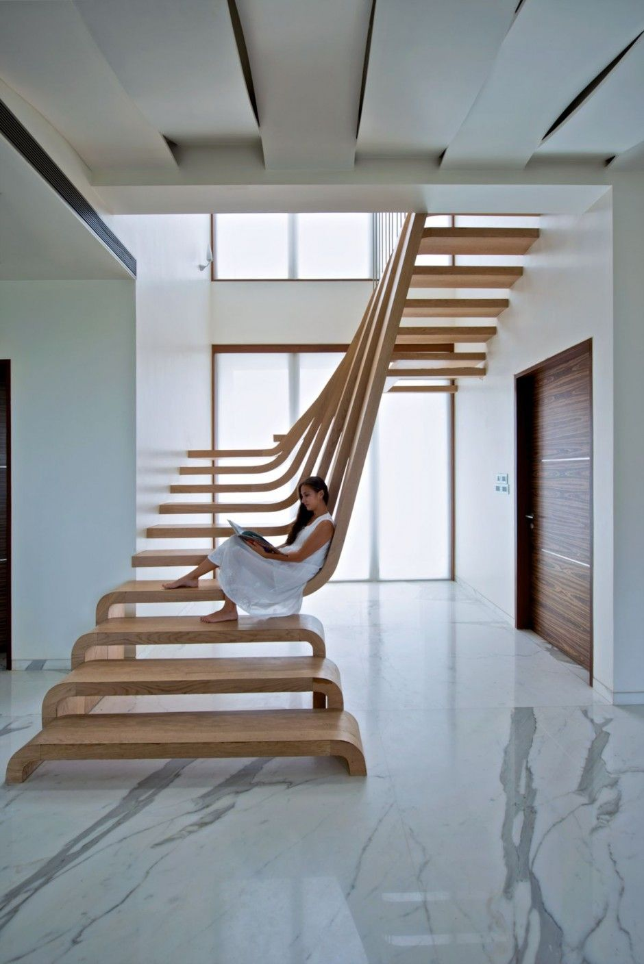 Sculptural staircase defines a modern two storey apartment for 2 story spiral staircase