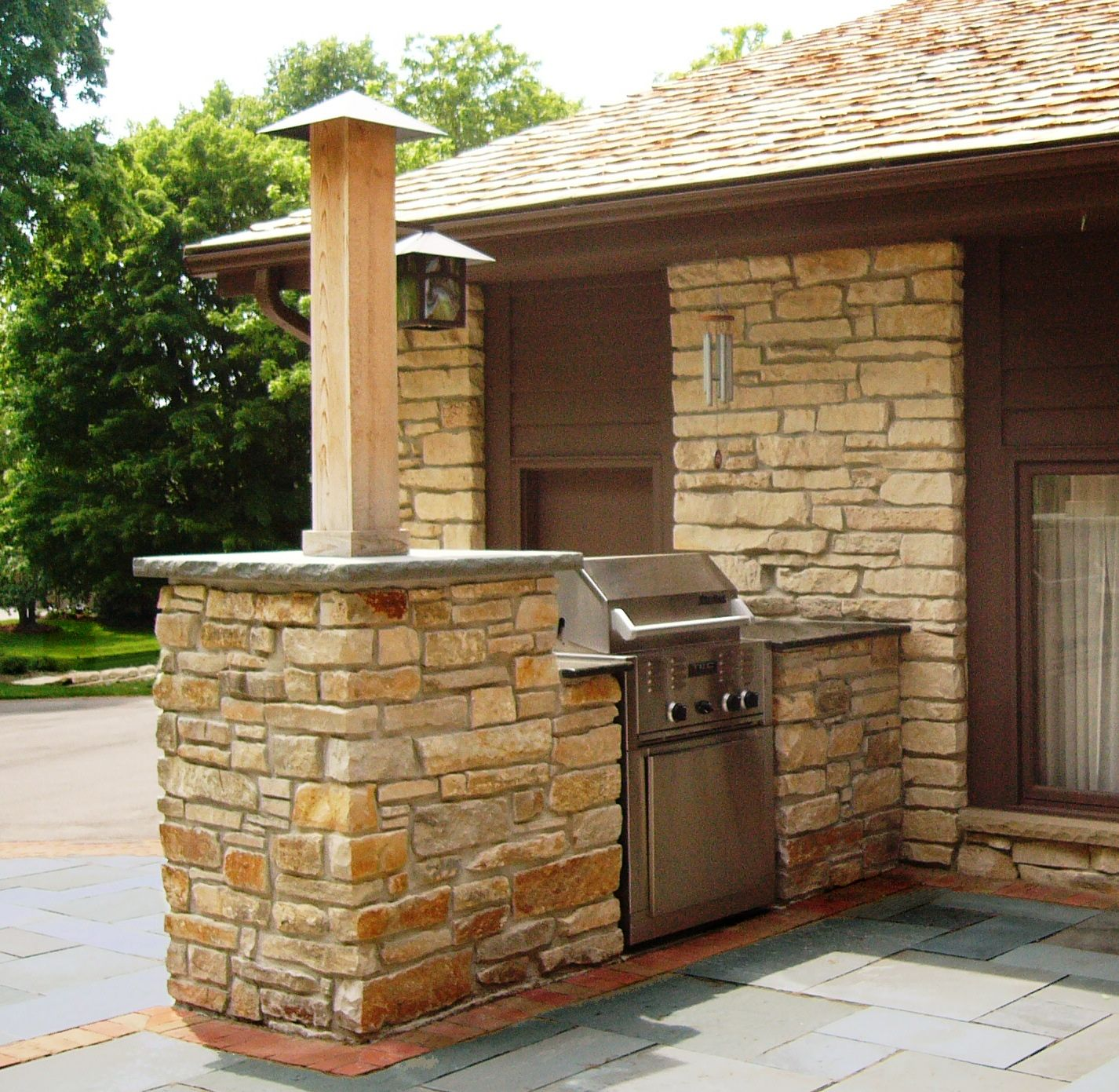 gas grill set in mortared lannon stone surround with bluestone cap and granite countertop on outdoor kitchen natural id=80519