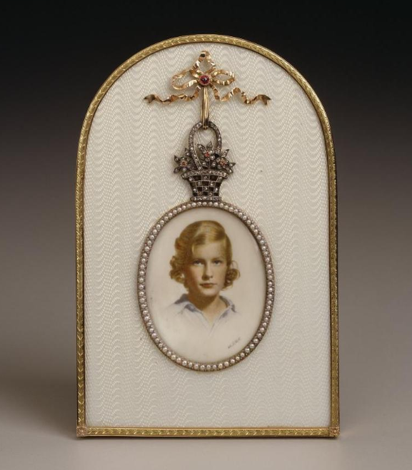 Fabergé frame, workmaster Mikhail Perchin. In translucent white enamel, applied with a gold basket of flowers with diamonds and rubies, supported by a gold bowknot set with a cabochon ruby. Narrow outer edge has leaves carved in green gold against red gold. Aperture bordered with seed pearls, portrait miniature of Dina Merrill Hartley (Nedenia Marjorie Hutton).