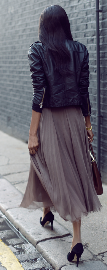 Black leather jacket, sleeves pushed, gray skirt, black heels, brown leather.  Very stylish.