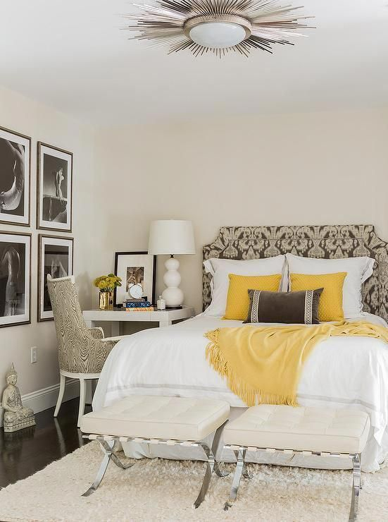 Gorgeous white and gray bedroom with pops of yellow is furnished with two ivory leather x-stools placed on an ivory sheepskin rug at the foot of a gray ikat bed complemented with white hotel bedding topped with a yellow throw and matching yellow pillows. #yellowbedroom #graybedroomwithpopofcolor