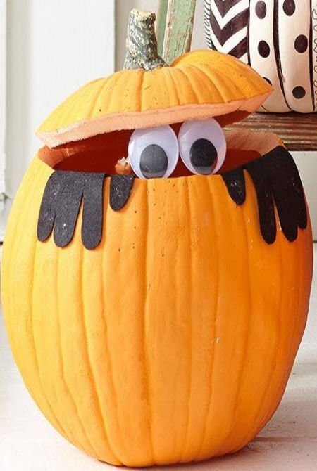 Gloves and big eyes peeking out of a carved pumpkin