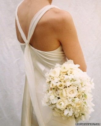 An exquisite all-white cascade like this one, fashioned from roses, sweet peas, Ranunculus, and tiny lilies of the valley, would be fitting for just about any bride in any setting. Dress by Robert Danes.