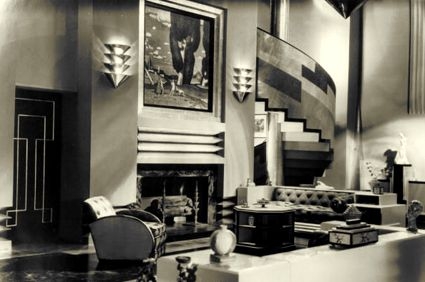 Art Deco's oversize elegance as presented by Hollywood in 1930's films. The wall lamps continue the interlocking papyrus plant motif typical of Deco since the 1922 found of the tomb of Tutankhamun.