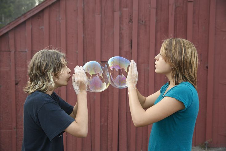 Teenagers blowing giant bubbles against a red barn.  Laurie Frankel Photography