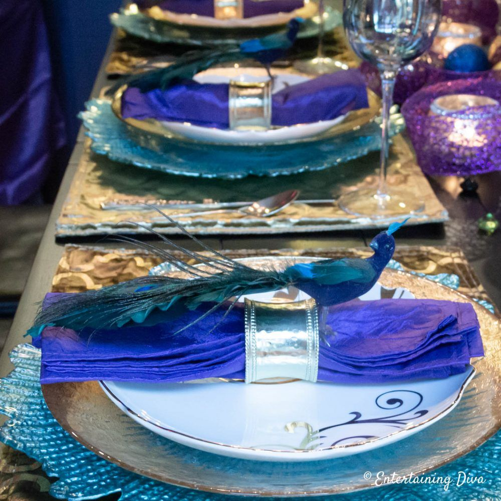 What a beautiful table setting with peacock colors! I love the gold and teal place setting and the purple napkins. It would be perfect table decor for a birthday party or wedding. #entertainingdiva #tablescapes #tablesetting #peacock
