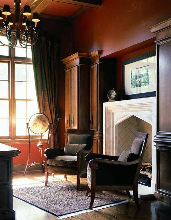 Masculine Room With Rust Colored Walls Built In Cabinets Coffered Ceiling And Stone Tudor Arch Fireplace Rust colored walls living room