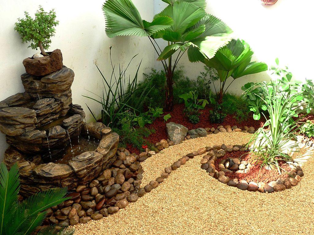 Jardin peque o con fuente de agua palmas piedras y for Como decorar un patio con pileta