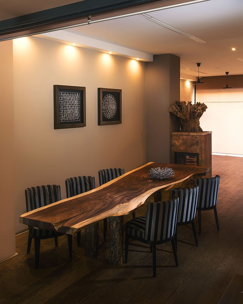 handcrafted dining table with live edges and stone base by OSTROLUCKY