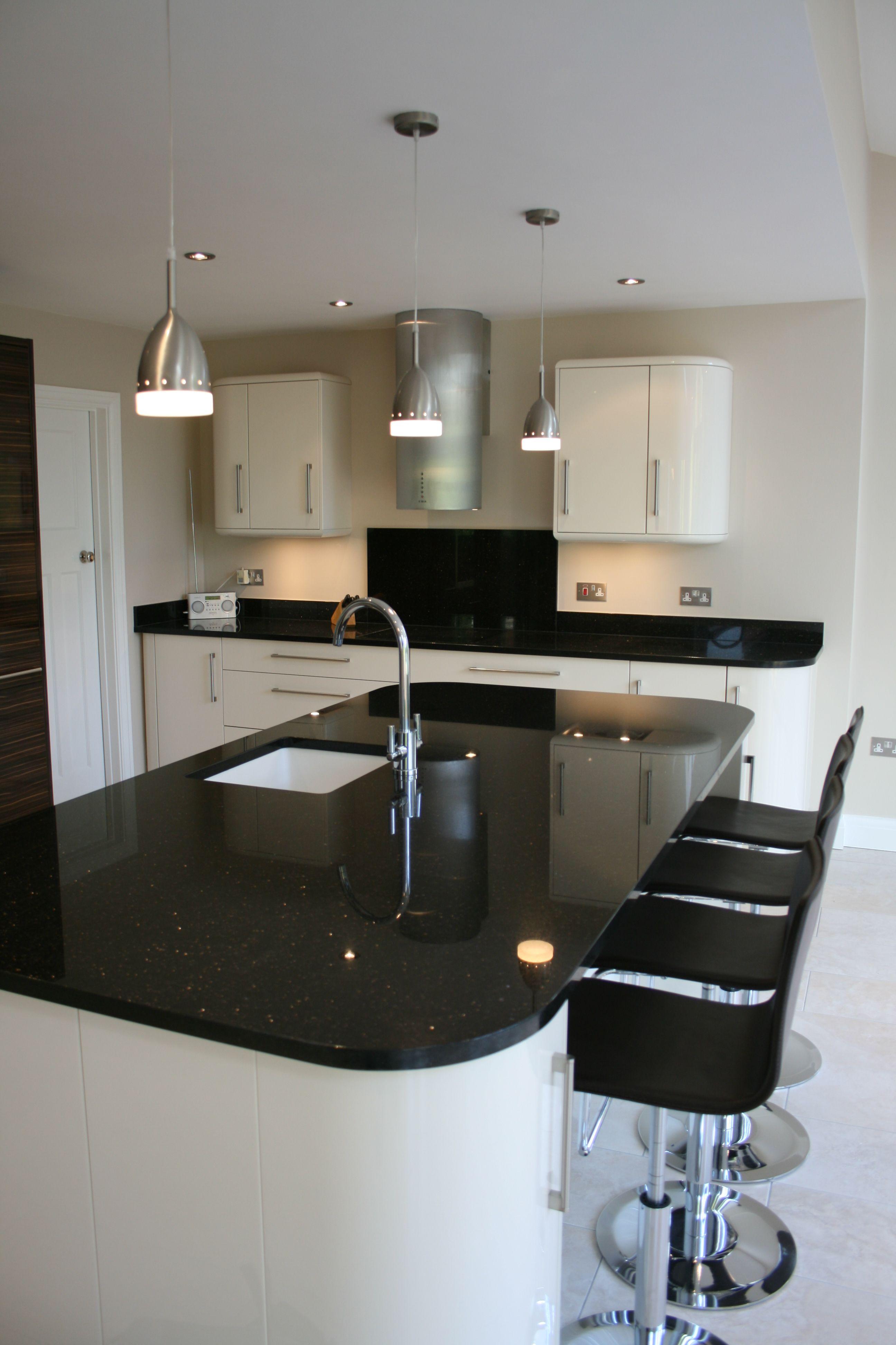 Contemporary Kitchen Island Incorporating Wine Fridge Storage Cupboards Undermount Sink And Bar Seating
