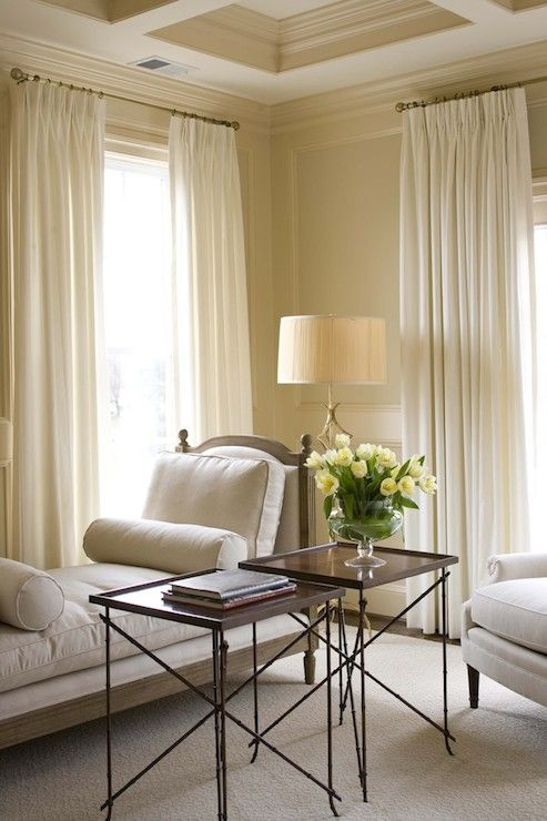 The Bedroom Walls Features Raised Wainscoting And Coffered Ceiling Painted  In Beige Beside Ivory Floor Length Drapes.