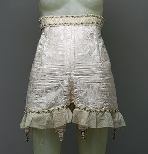 """Silk damask girdle, American or European, 1924. This heavy damask girdle has much of the force and structure of a nineteenth-century corset brought to bear on the hips rather than the waist. It had an overall slimming effect since, as noted in a 1923 girdle advertisement, """"Being slim may be a matter of pounds, but looking slim is a matter of where those pounds are placed."""" A substantial undergarment such as this one could easily move several pounds around on the body and it serves as an…"""