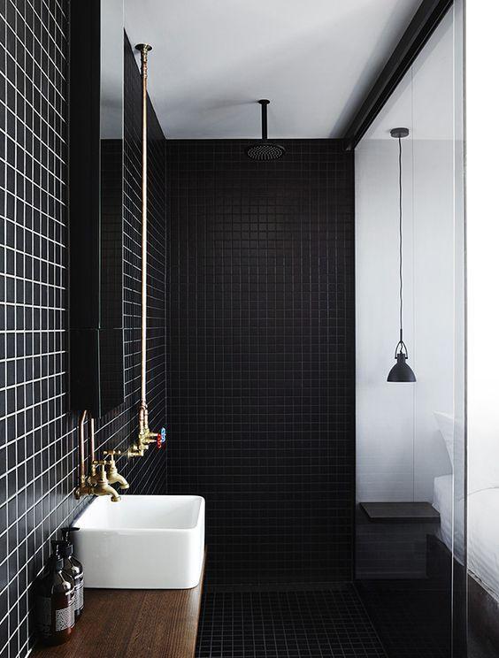 Industriele badkamer met simpele badkamermeubel en zwarte tegels ...