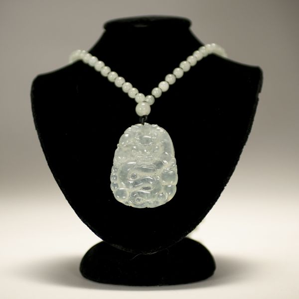 Icy Jade Pendant Necklace - icy jadeite  carved dragon in low relief, on a matching string of one hundred round icy jadeite beads -  $1200 at auction