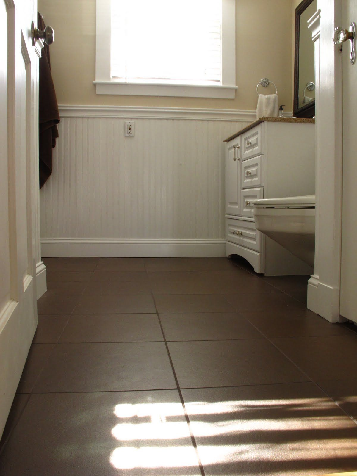Dark brown tile in bathroom floor white subway tile in for Flooring tiles for bathroom