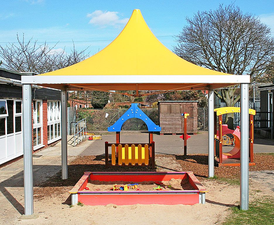 A yellow peak style canopy installed over a children's play sand area for shade.