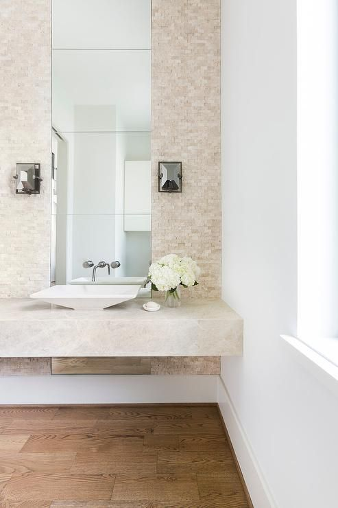 contemporary powder room featuring a cream floating vanity