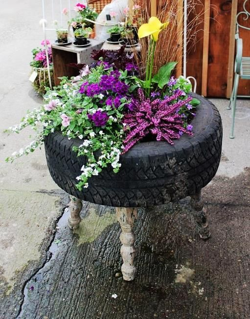 Upcycled Tire into pretty and durable garden flower planter, add wooden legs…