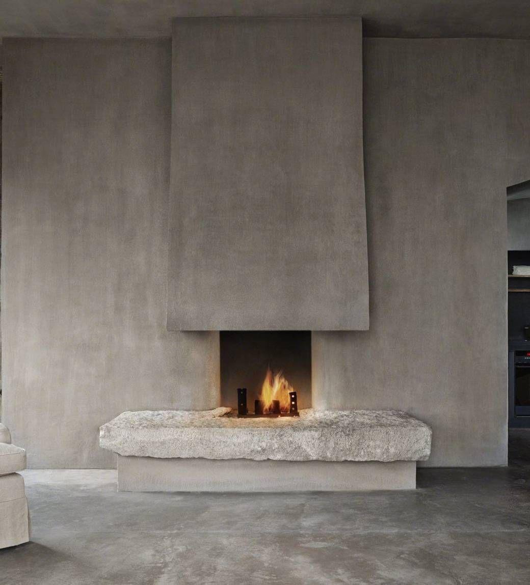 Design ambiente rustico con il camino in cemento che presenta una particolare soglia in pietra di grandi dimensioni