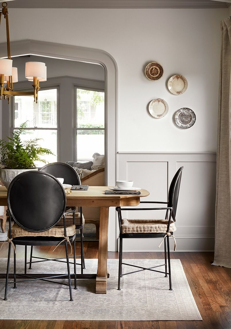 Classic decor inspiration in this dining room with light grey painted wainscot, gothic archway, plates on the wall, and modern dining chairs. #fixerupper #diningroom #decorinspiration #lightgrey