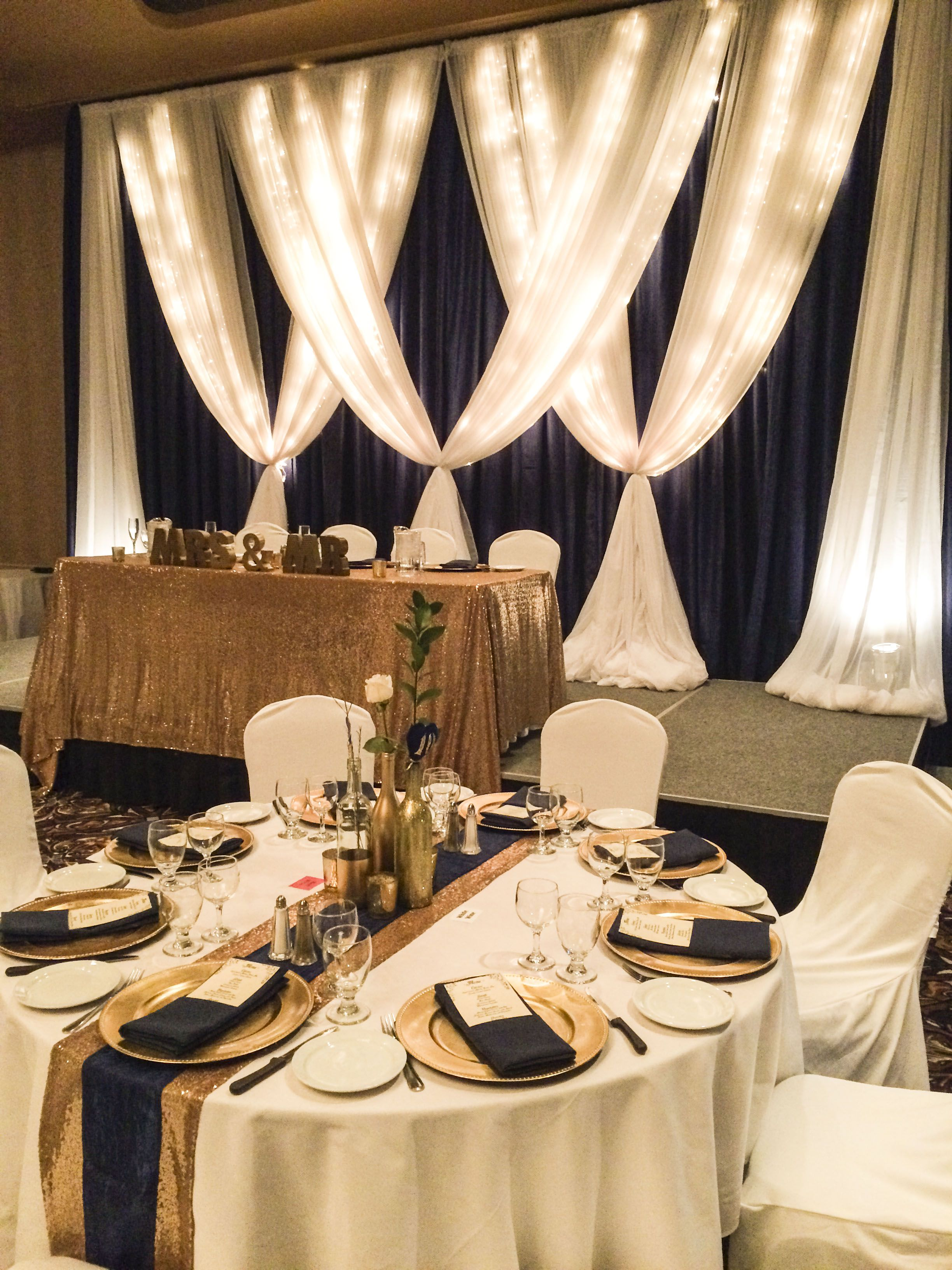 Glittery Gold and Navy Wedding #lethbridgeeventrentals #lethbridgeevents # wedding #wedding… | Head table wedding backdrop, Wedding table settings, Wedding  backdrop