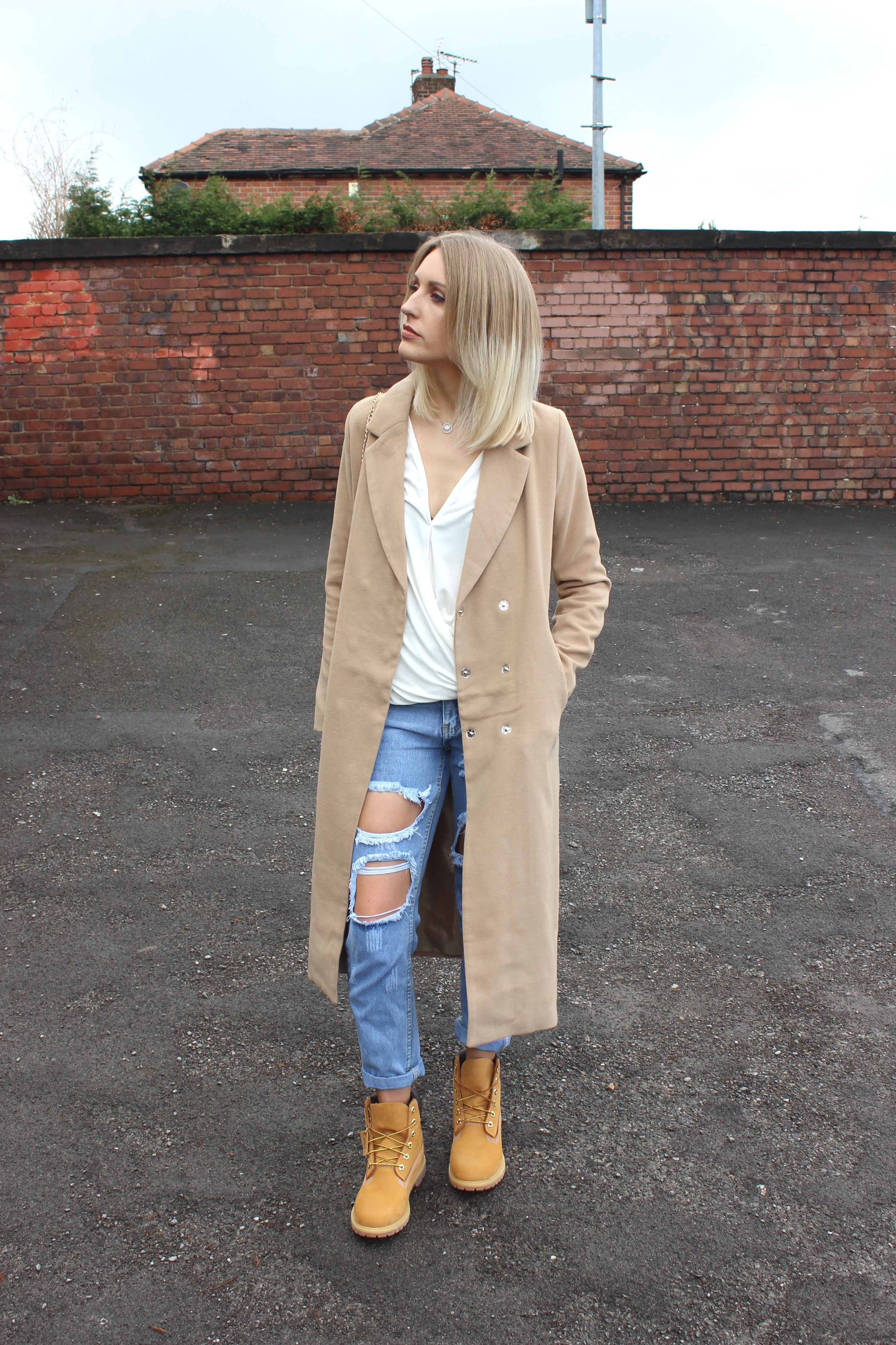 91430bc56111 How To Wear Timberland Boots for Women with ripped denim and a long coat   fashion  style  denim  timberlands