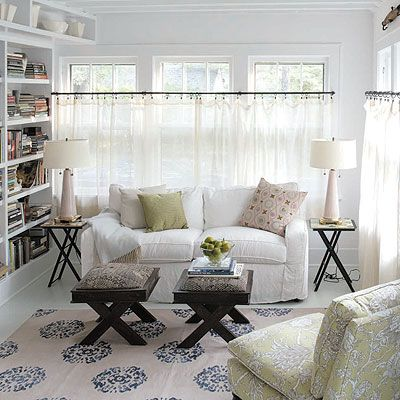 so bright and light...yet cozy. certain elements of this room I would love in my own sunroom.