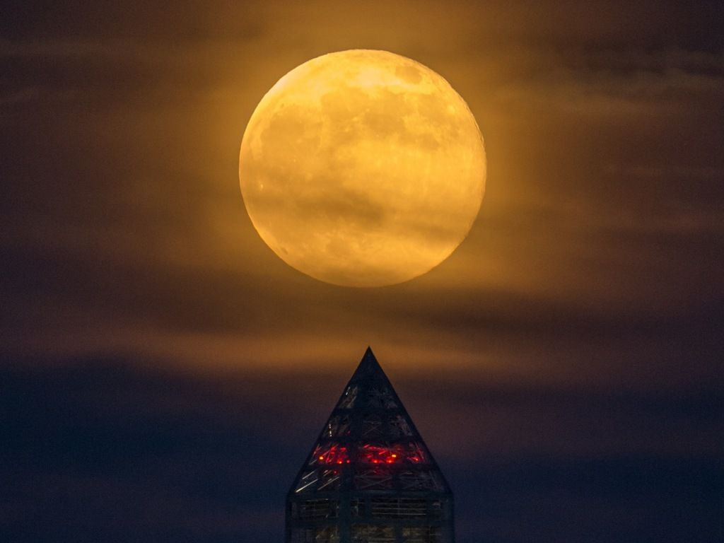 The June full moon, called the Strawberry Moon, occurs on Friday the 13th. Here a full moon climbs its way to the top of the Washington Monument, Sunday, June 23, 2013.