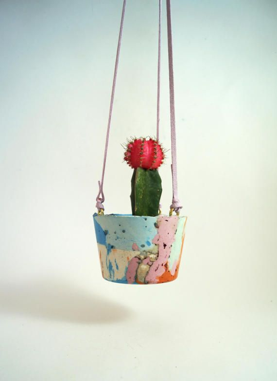 Beautiful hanging concrete planter with bright colour palette. Little brass hooks with faux leather strings for hanging.  This item is carefully hand made from start to finish by Emma McDowall - an artist & maker based in Scotland. Each piece is completely unique in design, and many moulded from recycled materials. Size: height 7cm x circumference 32cm. Depth: 5.5cm