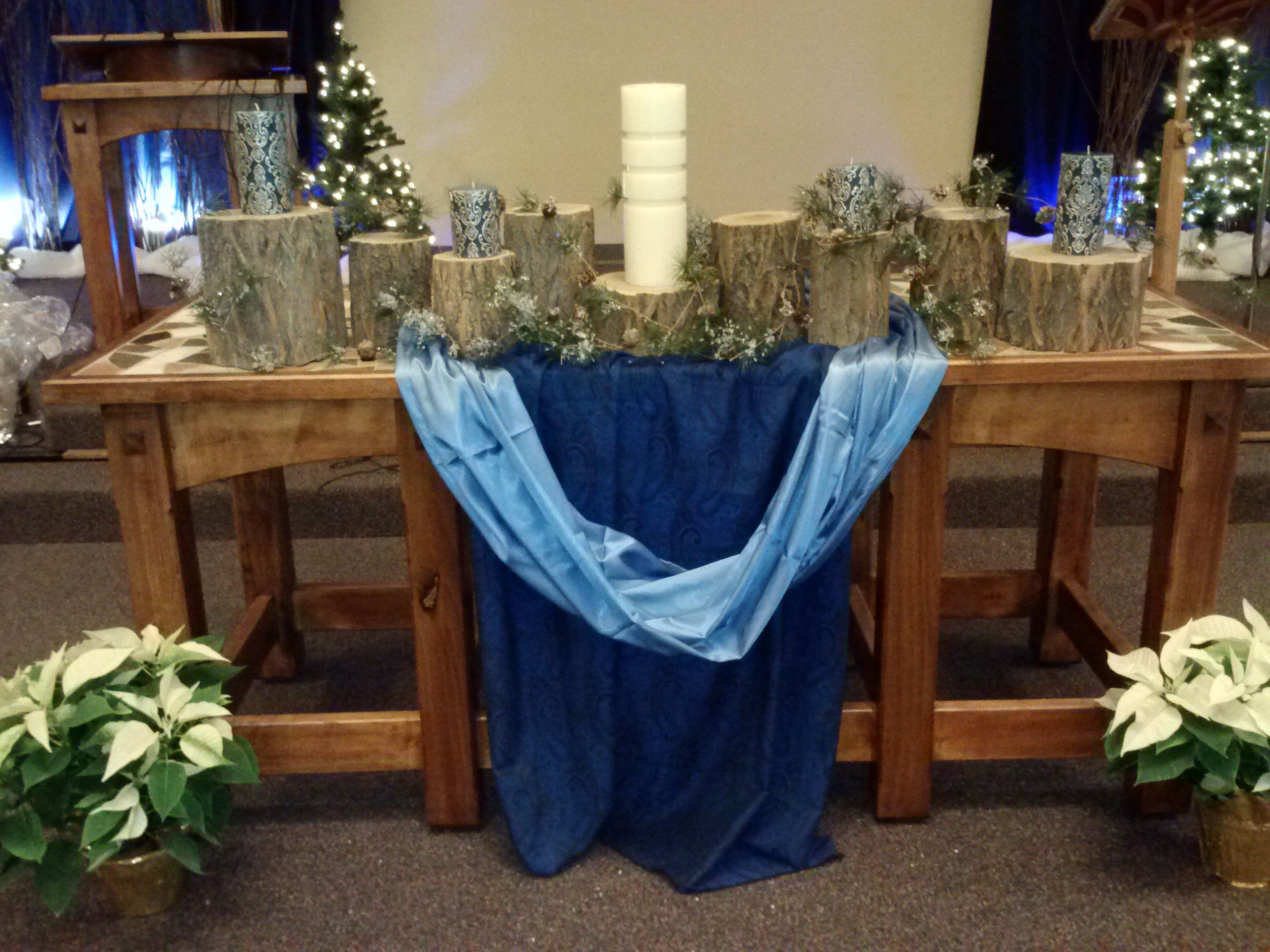 log rounds on communion table as an alternative advent wreath. would