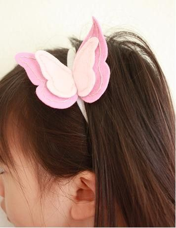 Pink felt butterfly on a soft white nylon headband. $12.00, via Etsy.