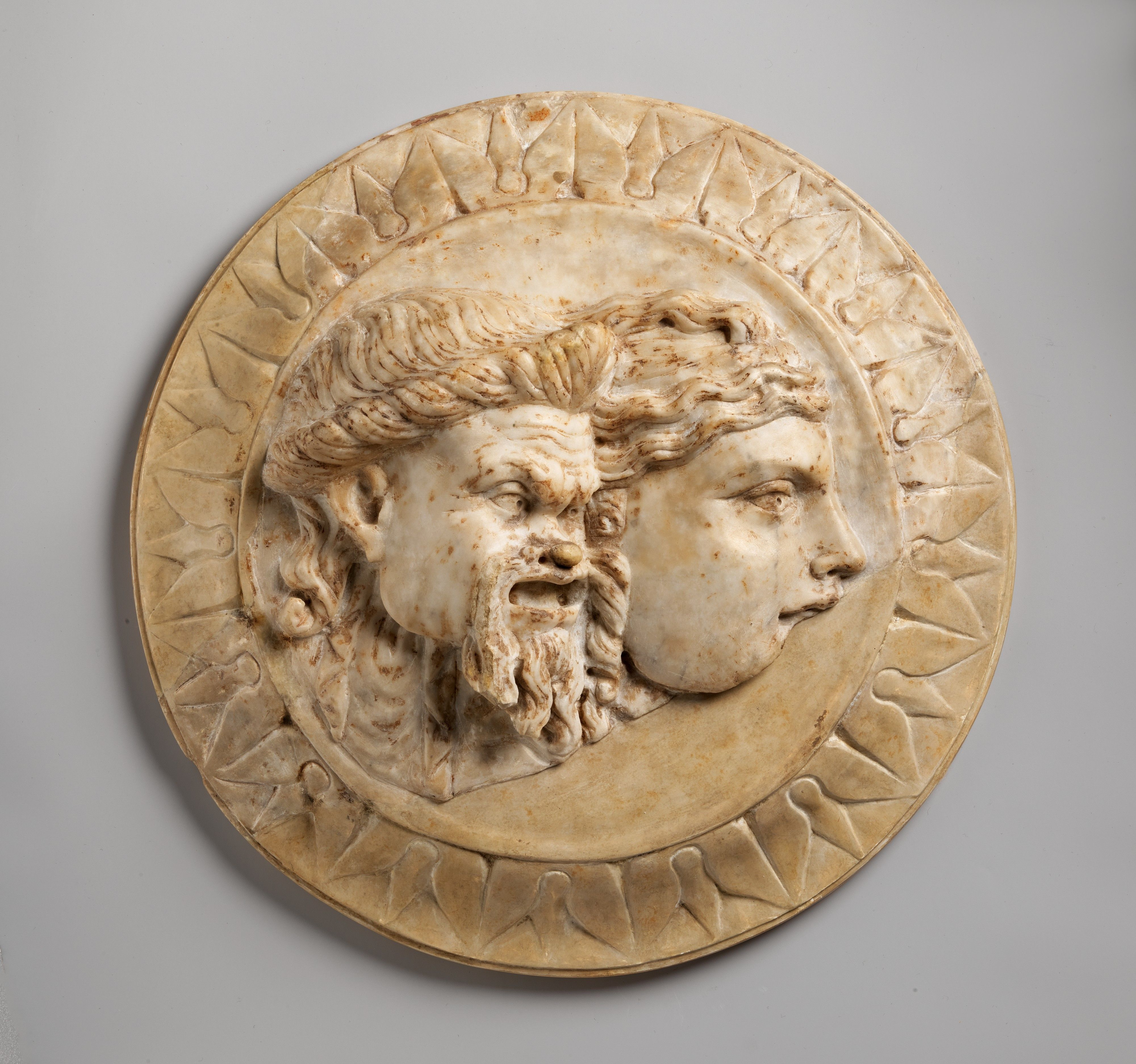 Marble disk with two theater masks in relief. Period: Early Imperial. Date: 3rd quarter of 1st century A.D. Culture: Roman.
