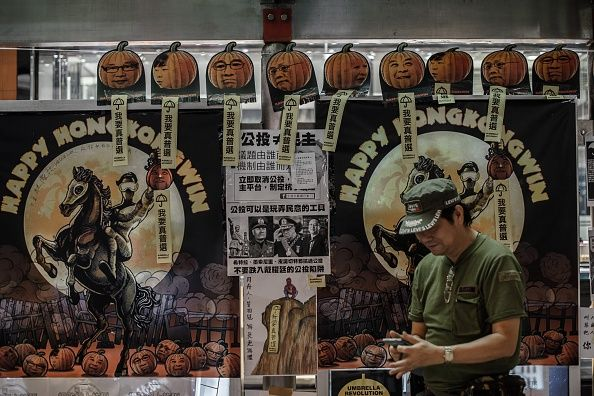 Umbrella Revolution Hong Kong, A man checks his mobile phone in front of halloween posters made by pro-democracy protesters depicting politicians as pumpkins heads at a protest site in the Mongkok district of Hong Kong on October 26, 2014. Four weeks after tens of thousands of Hong Kongers took to the streets demanding free leadership elections for the semi-autonomous Chinese city, weary demonstrators remain encamped across several major roads. AFP PHOTO / Philippe Lopez