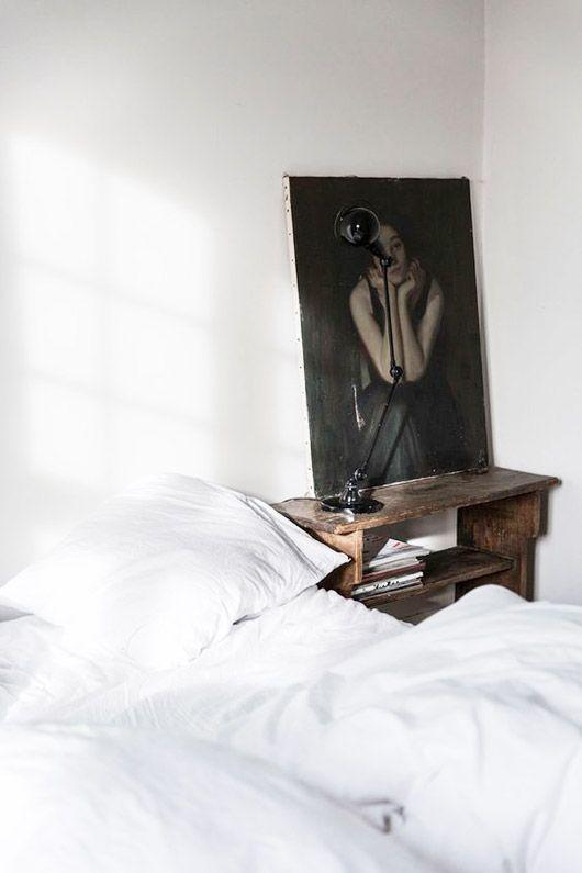 dark portrait painting on wood nightstand in white bedroom. / sfgirlbybay