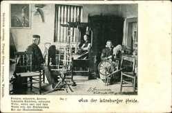Postcard Aus der Lüneberger Heide, Weberin bei der Arbeit am Webstuhl, Spinnrad
