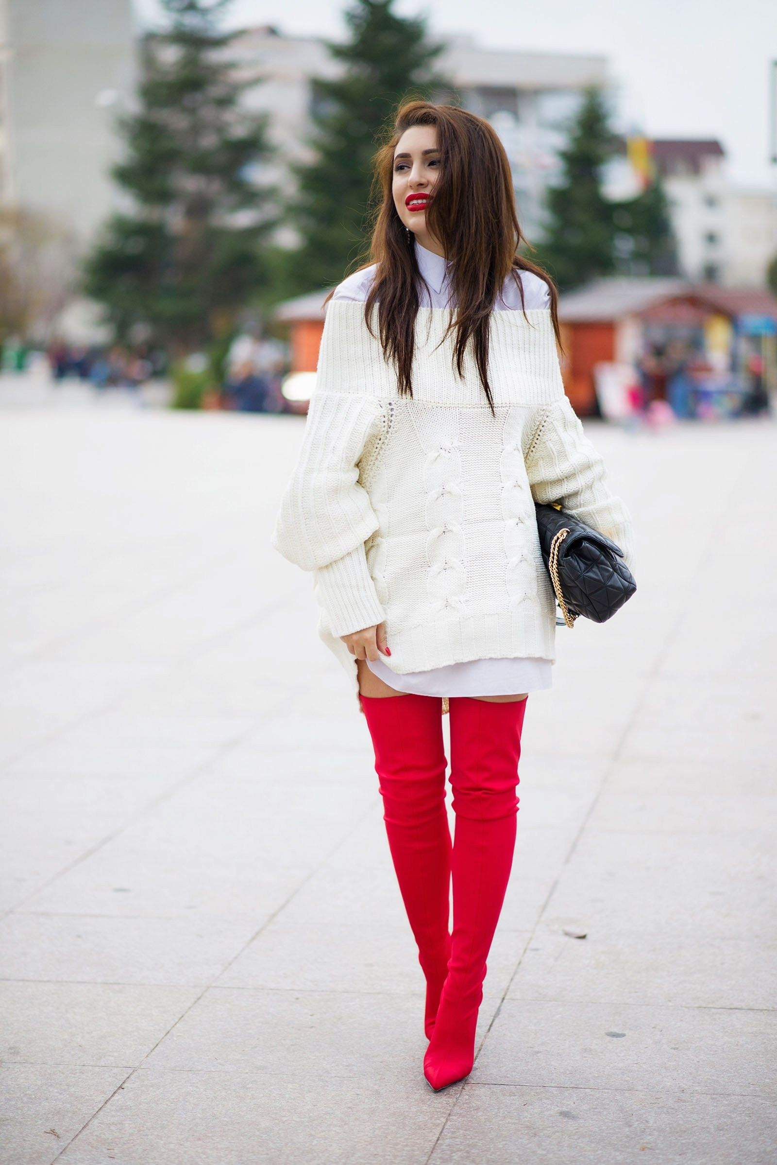 Andreea Manole wearing a pair of red thigh high boots paired with a white  shirt dress