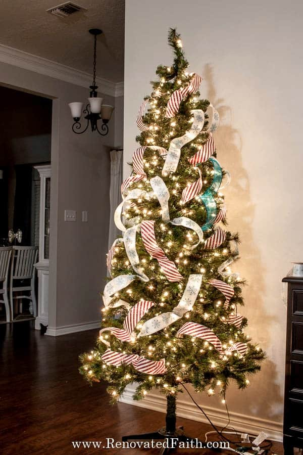 How to Add Ribbon to a Christmas Tree (& Christmas Tree Ribbon Topper) #ribbononchristmastreeideas HThe EASY WAY to Place Ribbon to a Christmas Tree – This STEP-BY-STEP tutorial with video shows you how to add cascading ribbon on Christmas trees.  Waterfall ribbon Christmas trees allow you to add any combinations of ribbon & mesh colors to customize your tree with satin or even flannel.  Ideas & DIY instructions on how to make ribbon garland for Christmas trees for any Christmas décor style i #ribbononchristmastreeideas